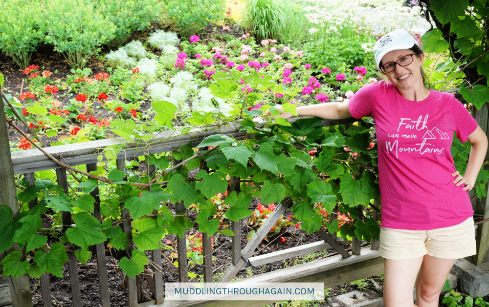 """White woman in a garden, wearing a pink t-shirt that says: """"Faith can move Mountains"""""""