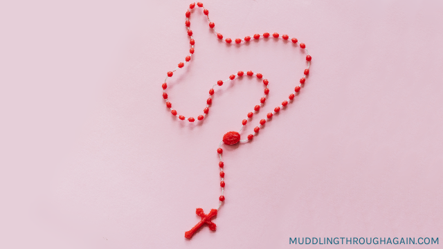 Red rosary beads on a pink table